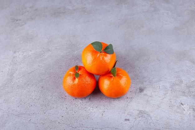 Ganze orange früchte mit grünen blättern auf steinhintergrund gelegt.