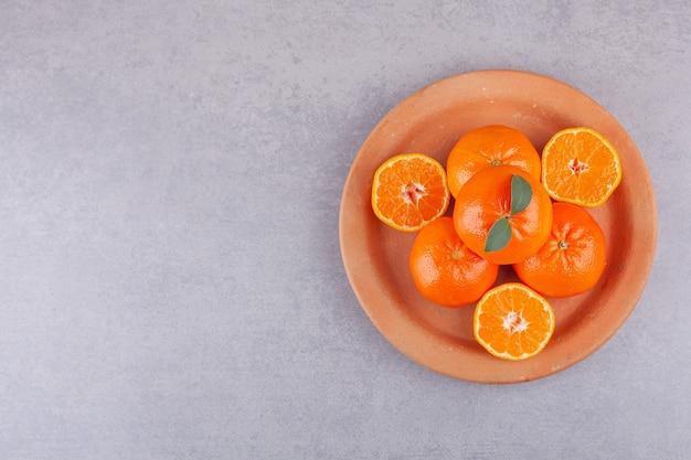 Ganze orangenfrüchte mit geschnittenen mandarinen auf tonplatte gelegt.