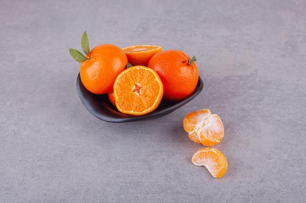 Ganze orangenfrüchte mit grünen blättern auf teller gelegt.