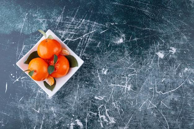 Ganze orangenfrüchte mit grünen blättern auf weißem teller.