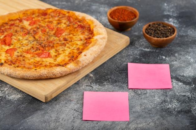 Ganze pizza mit gewürzen und aufklebern auf steintisch gelegt.