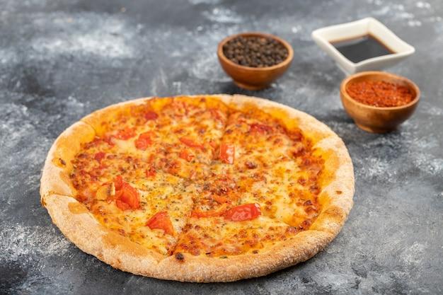 Ganze pizza mit gewürzen und sojasauce auf steintisch gelegt.