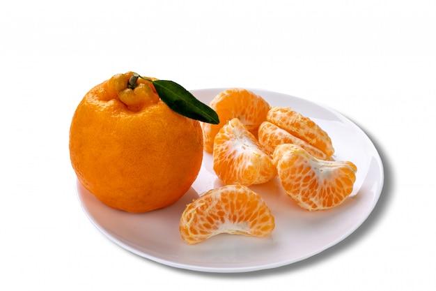 Ganze ponkan-mandarine und eine in segmenten auf einem teller geschält