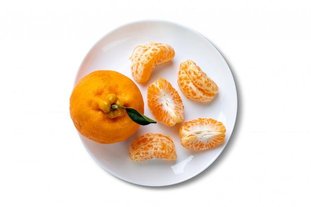 Ganze ponkan-mandarine und eine in segmenten geschälte platte auf weißem hintergrund. draufsicht