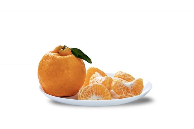 Ganze ponkan-mandarine und eine in segmenten geschälte platte auf weißem hintergrund.