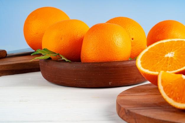 Ganze reife orangen in einer tonschale auf weißem tisch