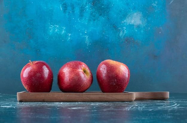 Ganze rote äpfel auf holzbrett.
