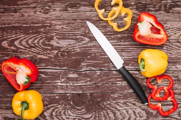 Ganze; scheibe und halbierte frische paprika mit scharfem messer auf holztisch