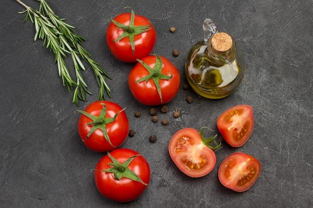 Ganze tomaten und gehackte tomatenschnitze, piment auf dem tisch. flasche olivenöl und rosmarinzweig. schwarzer hintergrund. draufsicht.