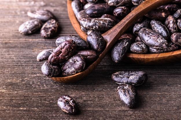 Ganze trockene kakaobohnen, pulver im hölzernen schüssellöffel auf alter rustikaler tabelle.