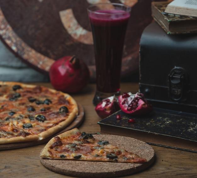Ganze und ein stück olivenpizza auf einem holzbrett