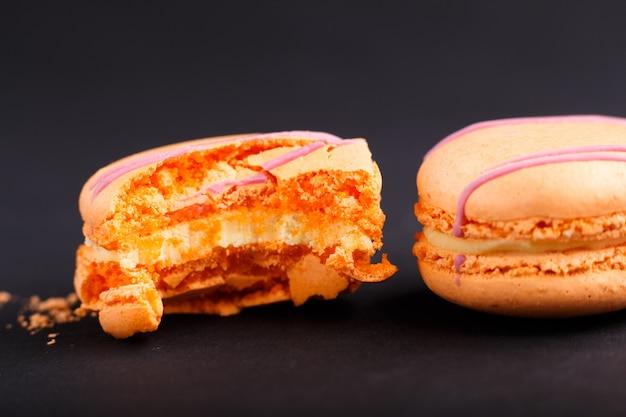 Ganze und gebissene orange macarons oder makronen backt auf schwarzem hintergrund zusammen