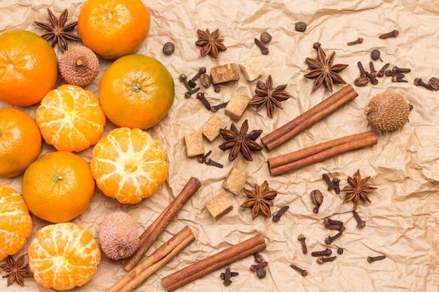 Ganze und geschälte mandarinen und gewürze. zimtstangen, sternanis, piment und kardamom, litschi und walnuss. hintergrund aus braunem papier. flach liegen