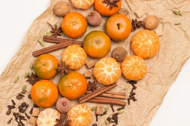 Ganze und geschälte mandarinen und gewürze. zimtstangen und sternanis, piment und kardamom, litschi und walnuss auf braunem papier. speicherplatz kopieren. weißer hintergrund. flach liegen