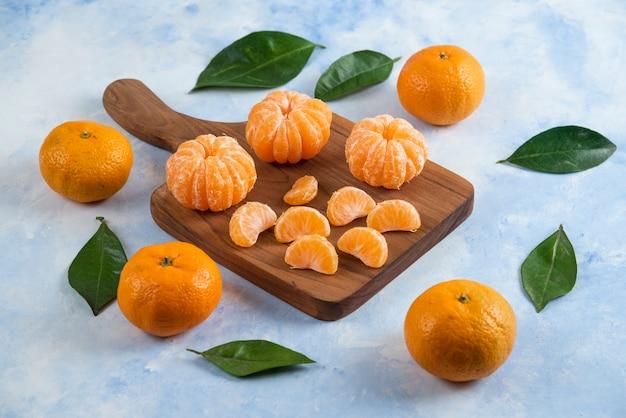 Ganze und geschälte scheibe clementinen-mandarinen. über holzbrett