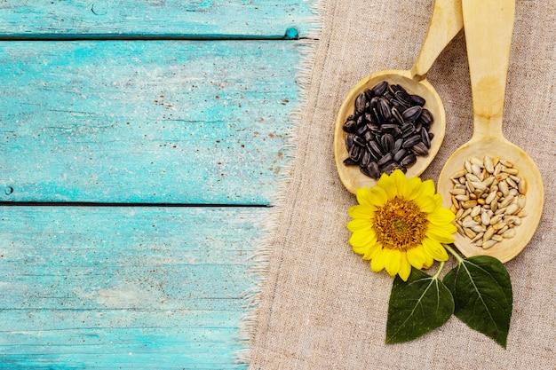 Ganze und geschälte sonnenblumenkerne und blüten