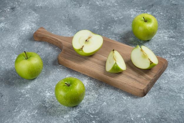 Ganze und geschnittene äpfel auf holzbrett.