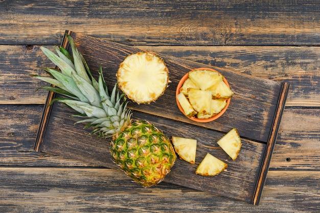 Ganze und geschnittene ananas in einem holzstück und einer tonschale auf einer holz-grunge-oberfläche. draufsicht.