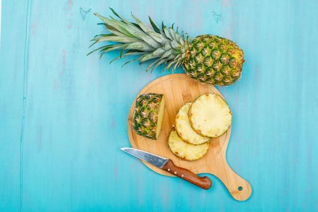 Ganze und geschnittene ananas in einem schneidebrett mit einer fruchtmesser-draufsicht auf einem blauen cyan