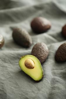 Ganze und geschnittene avocados auf grauem stoff