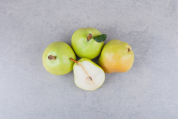 Ganze und geschnittene birnenfrüchte mit blättern auf einem dunklen tisch.