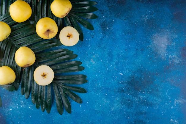 Ganze und geschnittene frische gelbe äpfel auf grünem blatt.