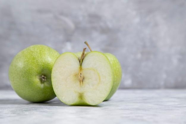 Ganze und geschnittene frische reife grüne apfelfrüchte auf marmorhintergrund gelegt. hochwertiges foto