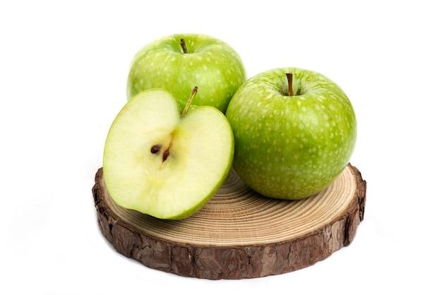 Ganze und geschnittene grüne äpfel auf holzstück auf weiß.