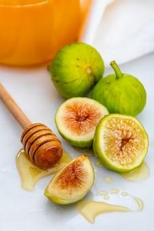 Ganze und geschnittene grüne feigen mit honig.