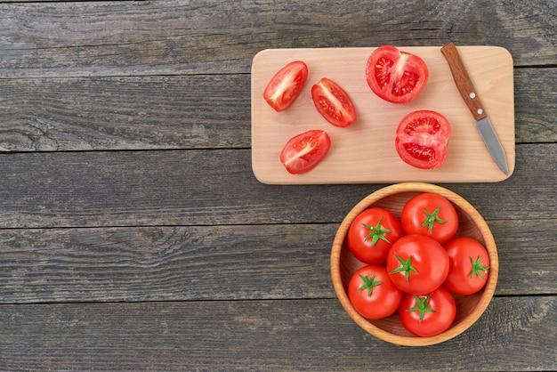 Ganze und geschnittene organische rote tomaten auf einem schneidebrett, draufsicht.