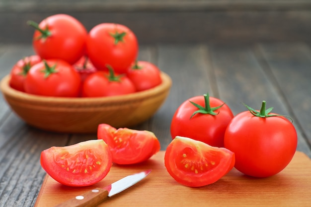 Ganze und geschnittene organische rote tomaten auf einem schneidebrett.