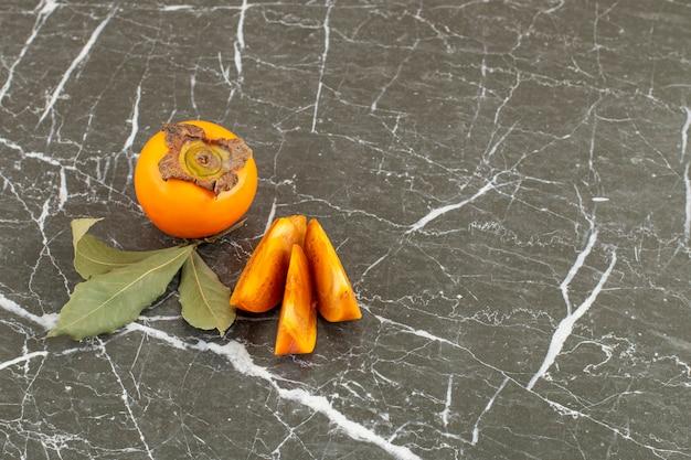Ganze und geschnittene persimone mit blättern auf schwarz