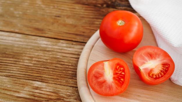 Ganze und geschnittene tomate auf einem holzbrett zum schneiden und holzhintergrund