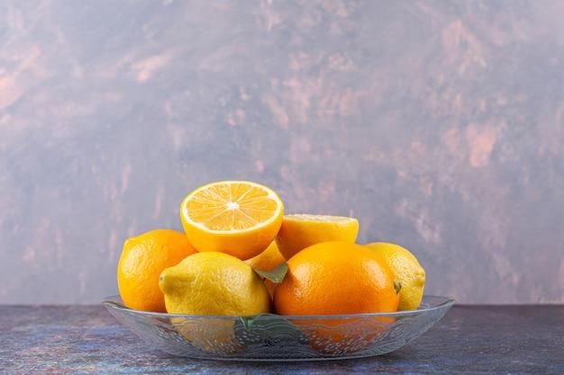 Ganze und geschnittene zitronenfrüchte in eine glasplatte gelegt.