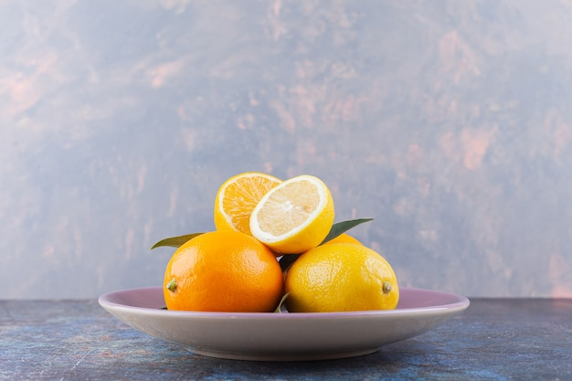 Ganze und geschnittene zitronenfrüchte mit blättern auf steintisch.