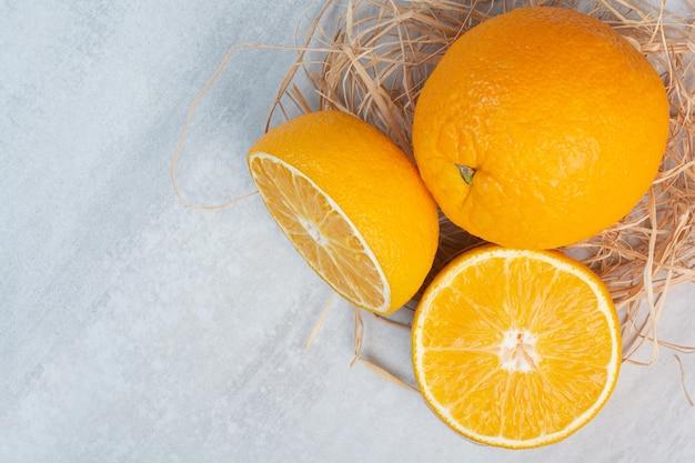 Ganze und halb geschnittene orangen auf steinhintergrund. foto in hoher qualität