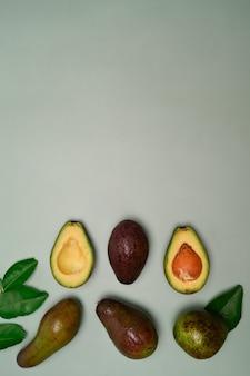 Ganze und halbe avocado auf grünem hintergrund.