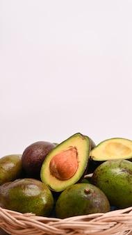 Ganze und halbe avocado in einem geflochtenen korb.