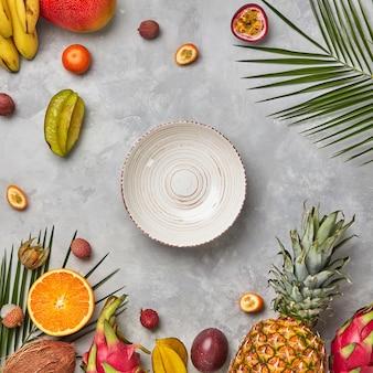 Ganze und halbe exotische gesunde früchte, karambole, ananas, passionsfrucht, pitahaya, palmgrüne blätter und ein leerer teller auf grauem betonhintergrund mit platz für text. flach legen