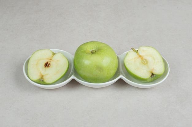 Ganze und halbe geschnittene grüne äpfel in weißen schalen