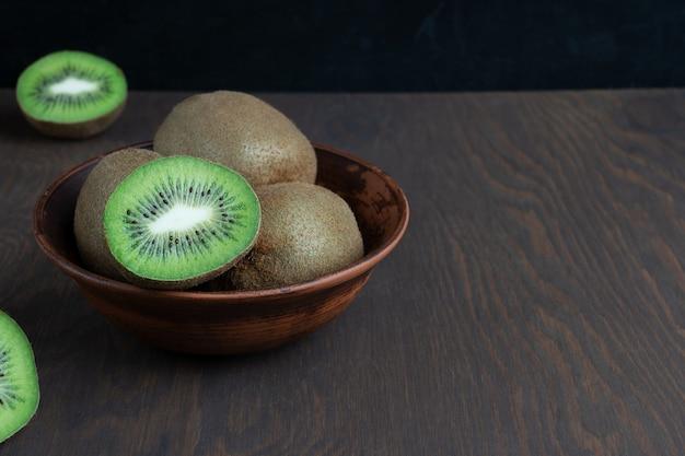 Ganze und halbierte reife grüne kiwis, serviert in einer braunen schüssel auf einem dunklen holztisch