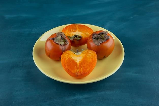 Ganze und in scheiben geschnittene kaki-früchte auf einen gelben teller legen.