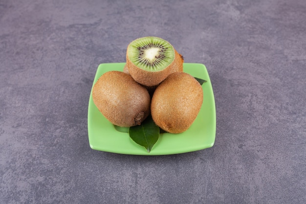 Ganze und in scheiben geschnittene köstliche kiwi mit blättern auf einem grünen teller.
