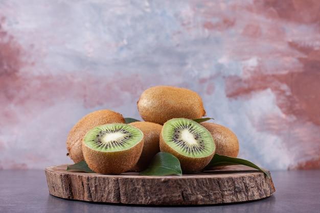 Ganze und in scheiben geschnittene köstliche kiwi mit blättern auf einem holzstück.