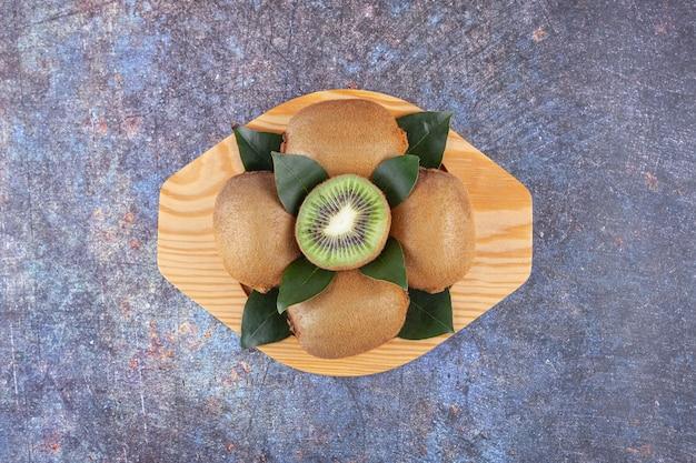 Ganze und in scheiben geschnittene köstliche kiwi mit blättern auf einem holzteller.
