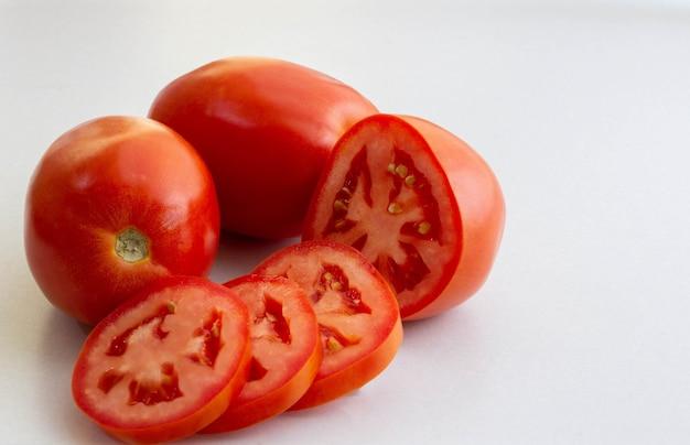Ganze und in scheiben geschnittene rote tomaten