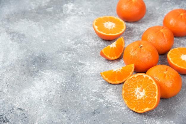 Ganze und in scheiben geschnittene saftige frische orangenfrüchte auf einen steintisch legen.