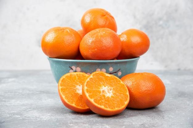 Ganze und in scheiben geschnittene saftige frische orangenfrüchte in eine schüssel auf einem steintisch stellen.