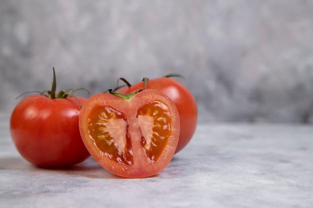 Ganze und in scheiben geschnittene saftige rote tomaten auf marmor gelegt