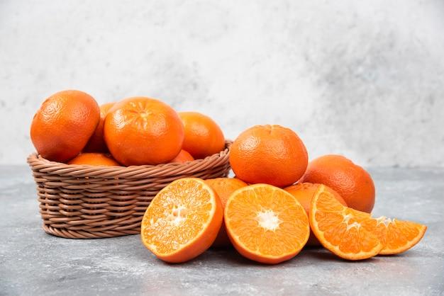 Ganze und saftige frische orangenfrüchte in einem weidenkorb auf einem steintisch in scheiben schneiden.